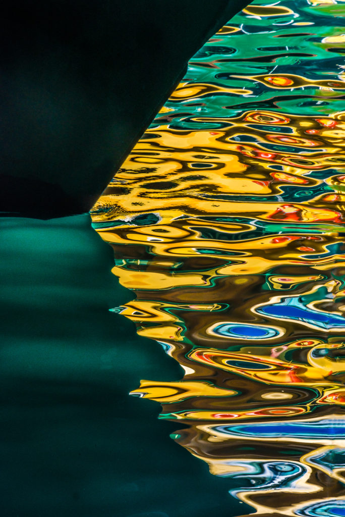 Colour photograph of rippling abstract pattern water reflection coming from Sydney Harbour ferries, Circular Quay, Australia