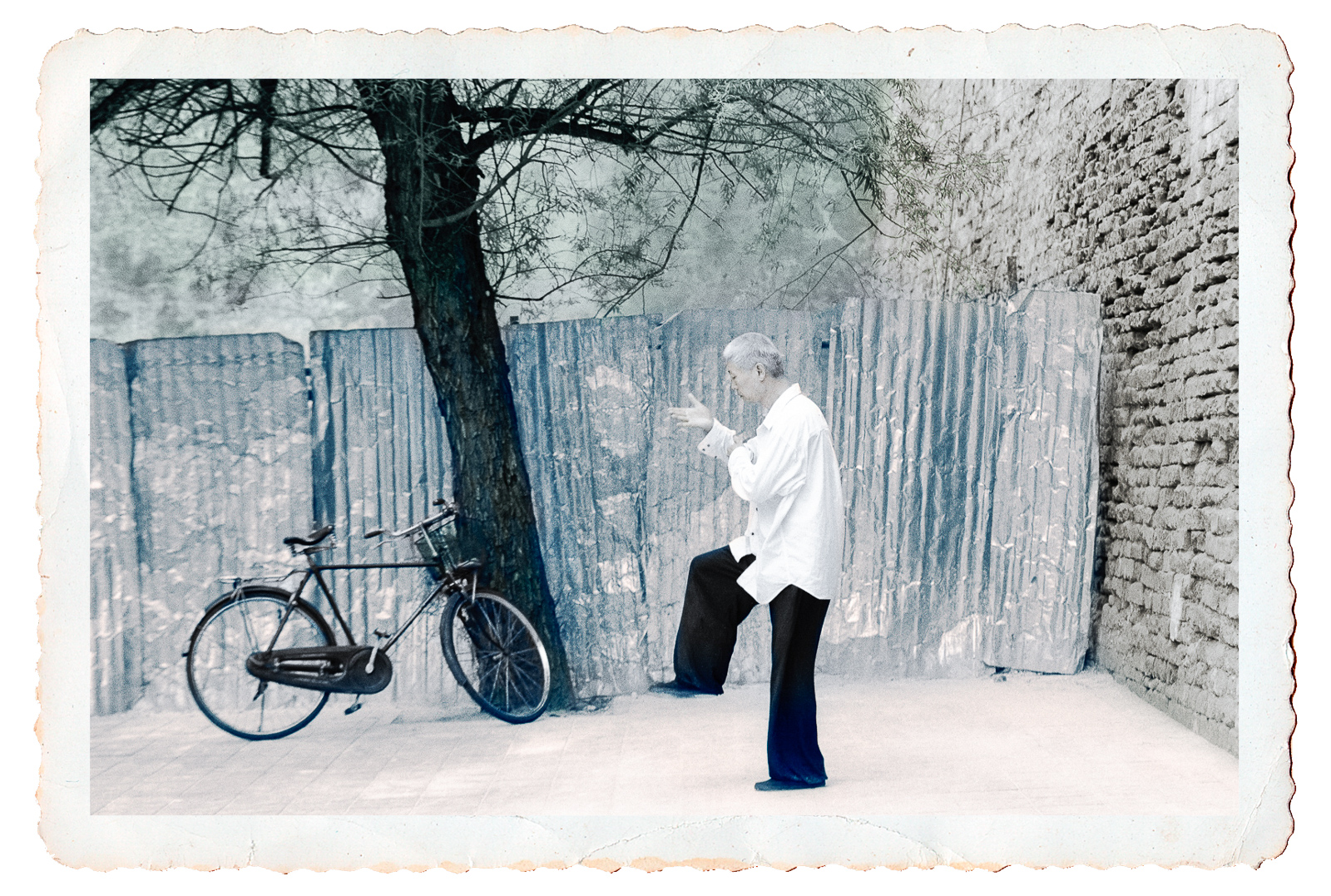 Hand-tinted photo of Man doing Tai Chi exercises in misty Beijing morning, China