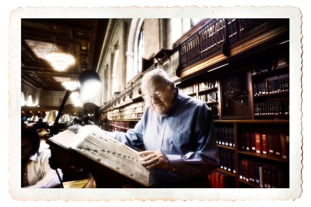 Postcard photo of an elderly man looking at large historical books in New York City Public Library