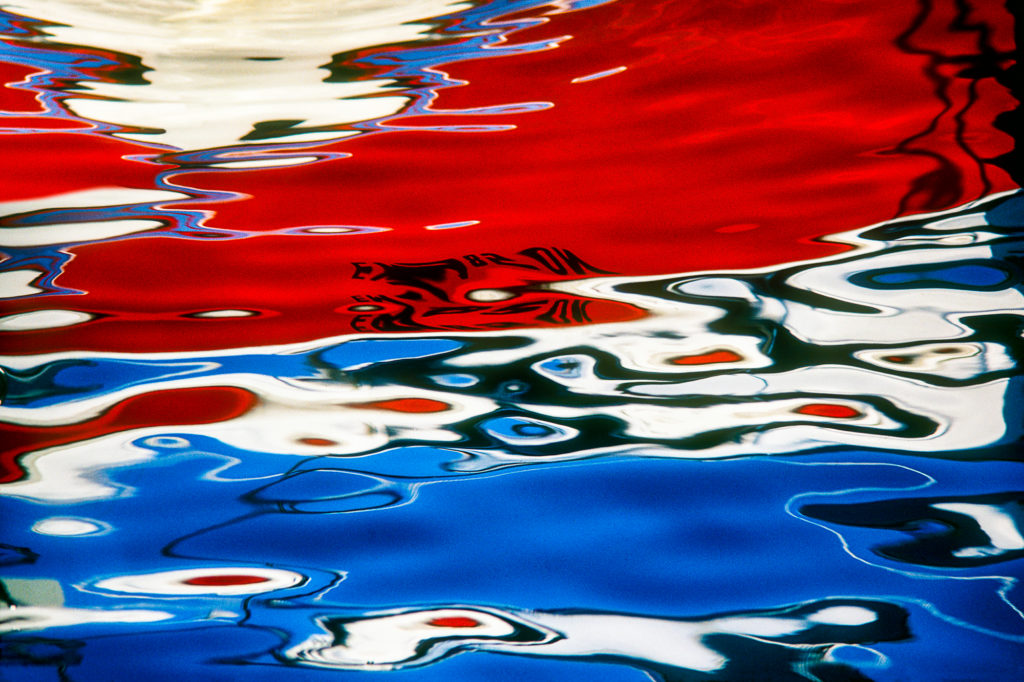 Abstract photograph of reflections, red white and blue from a boat